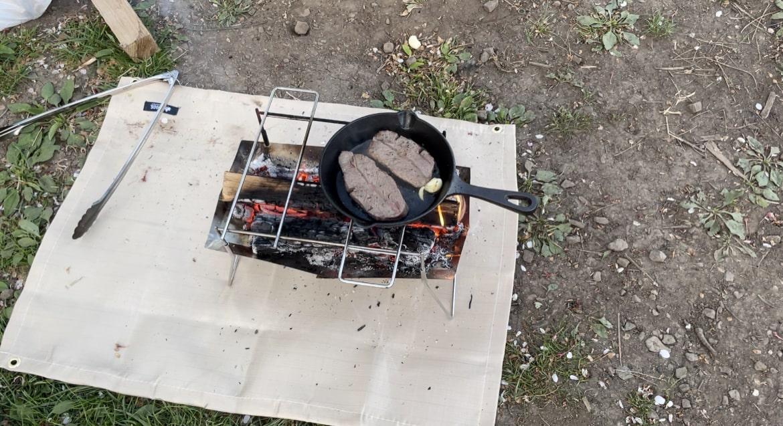 焚き火台の上にスキレットを乗せてステーキを焼いてます。
